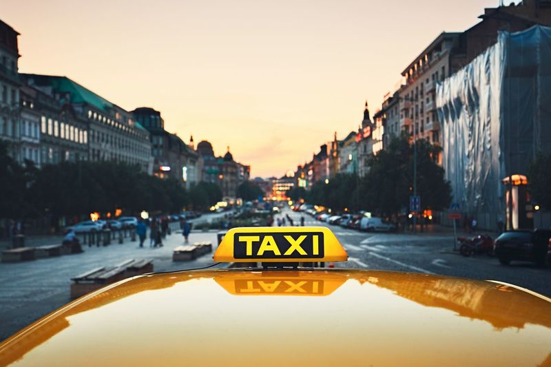 Close-up of taxi in city against sky