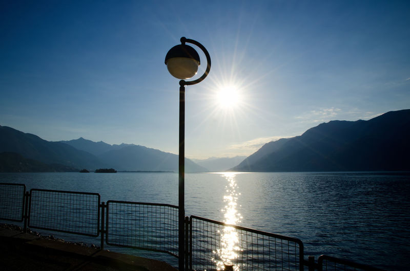 Street Lamp and Railing on Waterfront with Sunshine in Ticino, Switzerland. Backlit Beauty In Nature Clear Sky Day Idyllic Lake Lake Maggiore Mountain Mountain Range Nature No People Outdoors Railing Scenics Sea Silhouette Sky Street Light Sun Sunlight Sunset Swiss Alps Tranquil Scene Tranquility Water