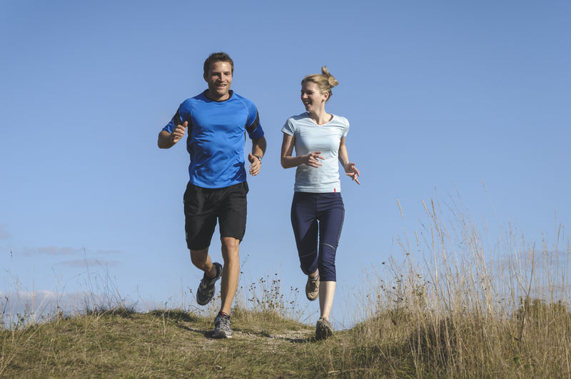Personal Training Personal Training Running Woman Clear Sky Day Fitness Fitness Training Front View Full Length Jogging Leisure Activity Lifestyles Men Nature Outdoors People Personal Trainer Real People Sport Sports Clothing Together Togetherness Two People Young Adult Young Men