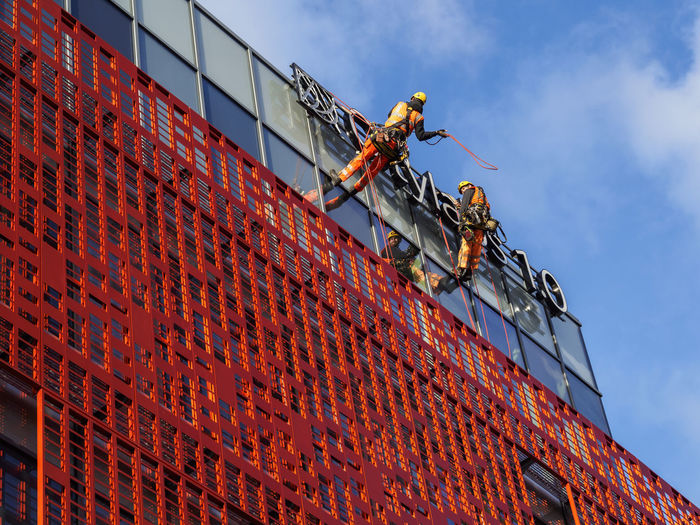 Abseiling workers on a building at Manchester Royal Infirmary wearing matching orange Abseiling Architecture Building Exterior Built Structure Hardhat  Industrial Equipment Industry Manual Worker Occupation Orange Color Rope Sky