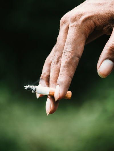 Close-up of cropped hand holding cigarette