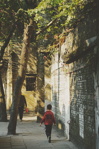 Kuaizi road in Foshan, China Architecture Building Exterior Buildings Built Structure Child China Kid Lifestyles Outdoors People Real People Rear View Shadow Street Streetphotography Sun Sunlight Tree Tree Wall