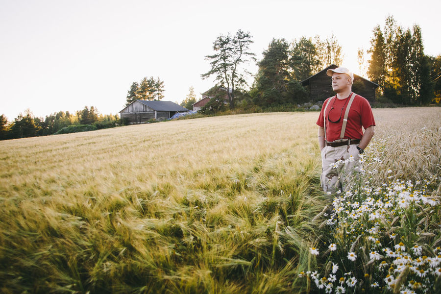 Agriculture Beauty In Nature Casual Clothing Day Field Field Full Length Grass Grassy Growth Harvest Harvest Time Hat Landscape Leisure Activity Lifestyles Man Nature Outdoors Plant Rural Scene Sky Tranquil Scene Tranquility Tree