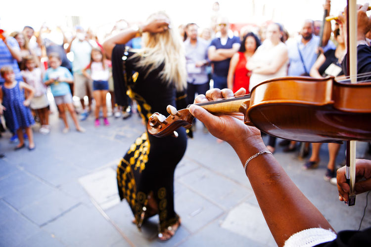 Cropped hand of street musician playing violin by dancing woman with people watching on street