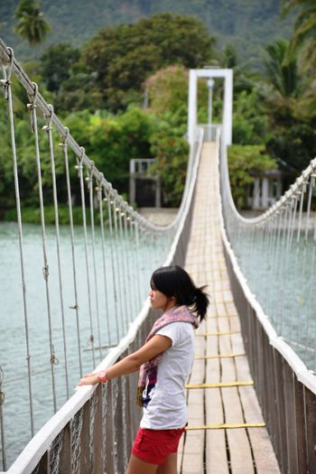 Young woman standing on rope bridge over river