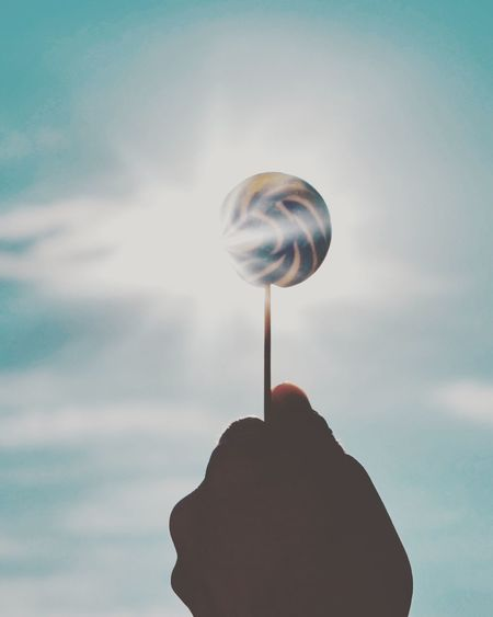 Chupa Sun Lollipop Eyeem Market EyeEm Masterclass Atmosphere Cloud - Sky Sky One Person Real People Nature Holding Human Body Part Human Hand Hand Low Angle View Unrecognizable Person Day Body Part Outdoors Balloon Leisure Activity Human Finger Lifestyles Finger