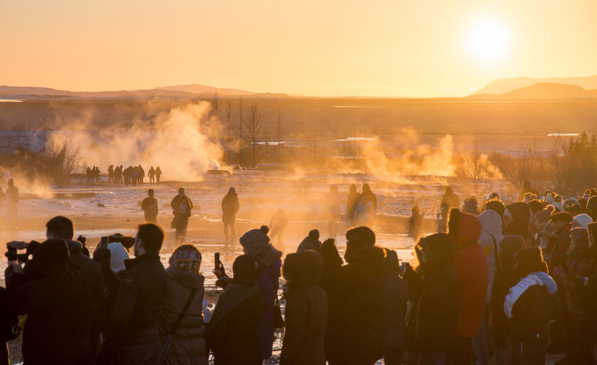 People by hot springs against sky during sunset