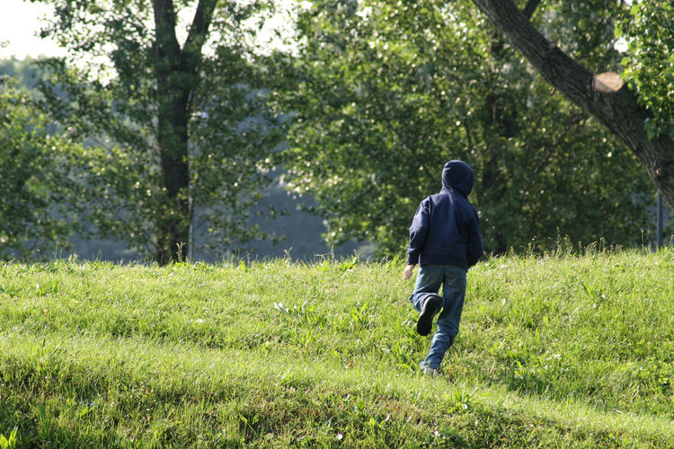 11 years old kid running away on a green hill in a park Copy Space Freedom Green Running Sunlight Young Blue Sweatshirt Casual Clothing Countryside Day Daylight Energy Grass Growth Healthy Lifestyle Kid Nature One Person Outdoors Park Rear View Running Away Spring Tree Young Adult