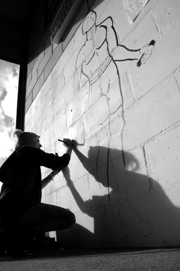 Real People Shadow One Person Wall - Building Feature Sunlight Men Day Full Length Lifestyles Nature Wall Sitting Architecture Outdoors Footpath Built Structure City Graffiti Leisure Activity Focus On Shadow