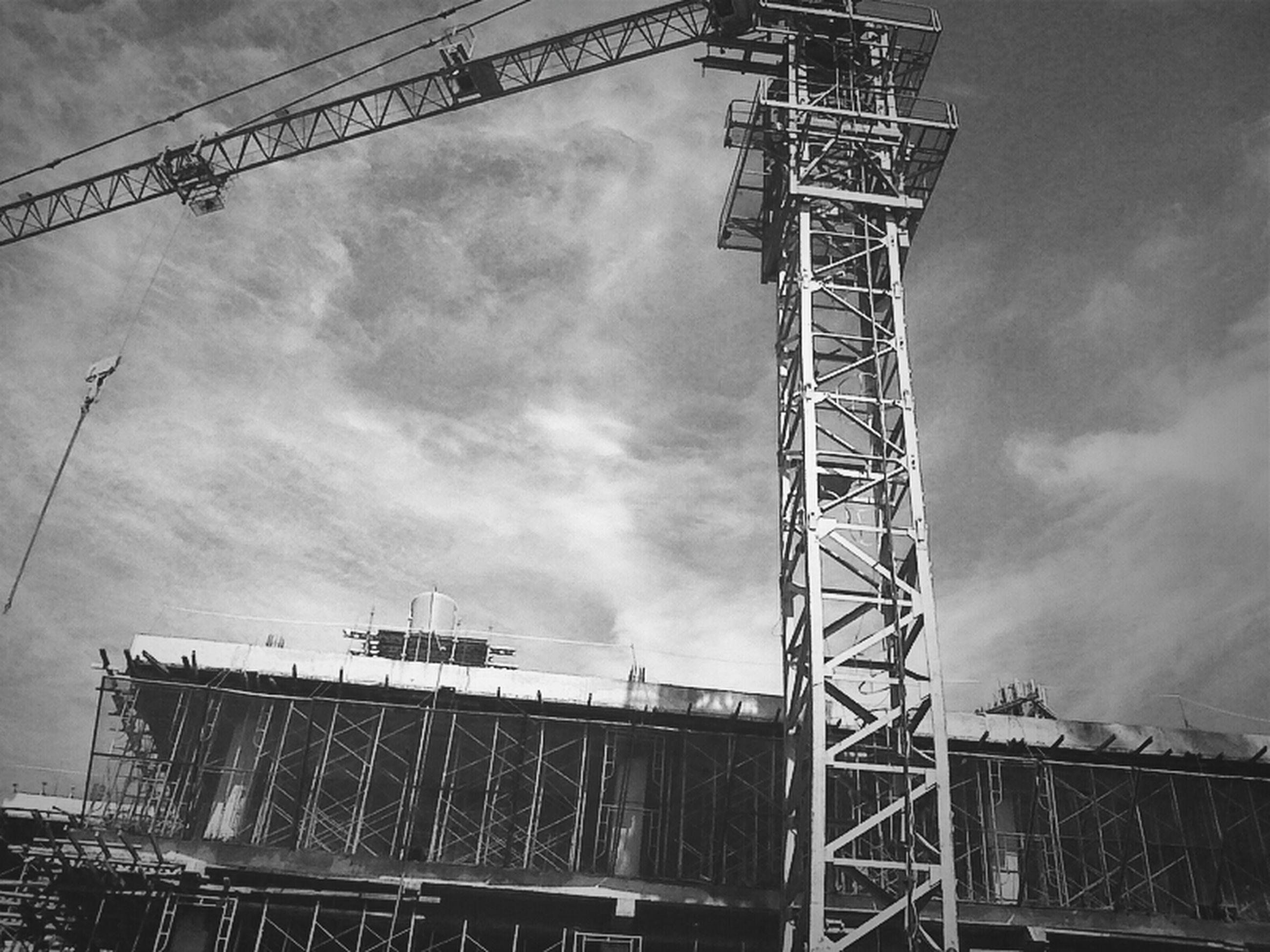 low angle view, sky, built structure, architecture, cloud - sky, connection, cloudy, construction site, metal, development, crane - construction machinery, tall - high, building exterior, cloud, electricity pylon, tower, industry, outdoors, no people, construction