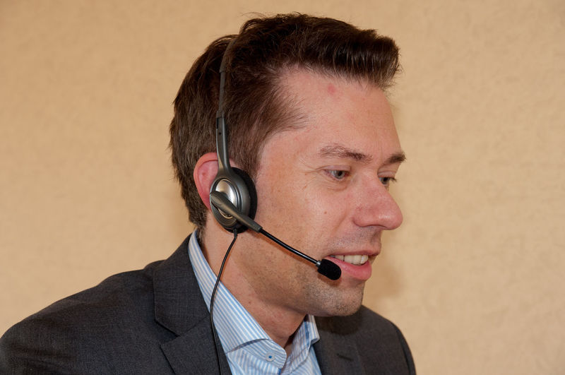 Close-up of businessman using headphones against wall