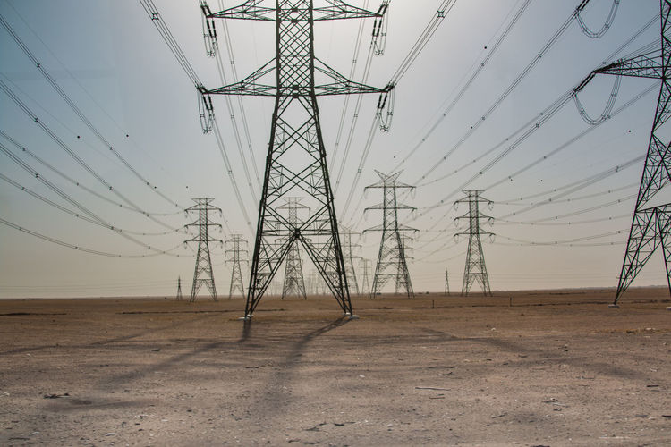 Electricity Pylons On Landscape Against Clear Sky