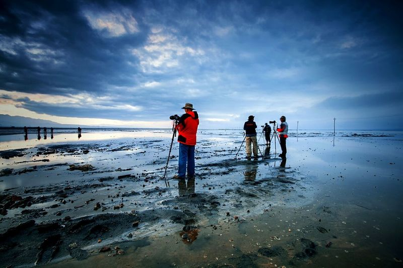 Photographers on wet shore against cloudy sky
