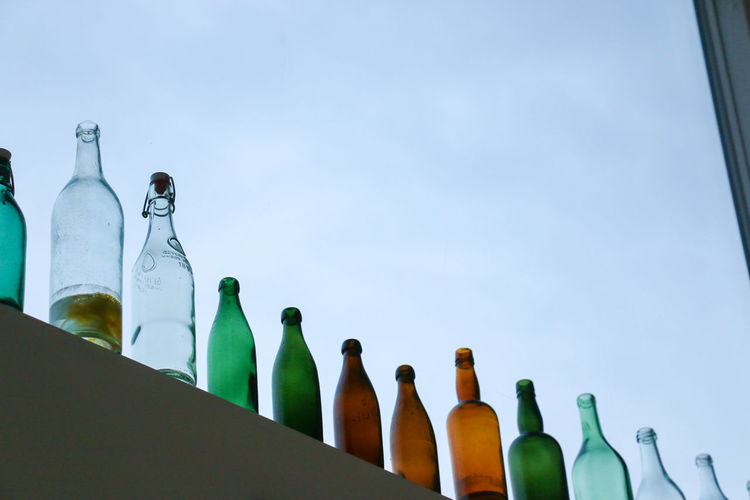 Low angle view of bottles against clear sky