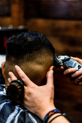 Cropped hand of barber cutting hair