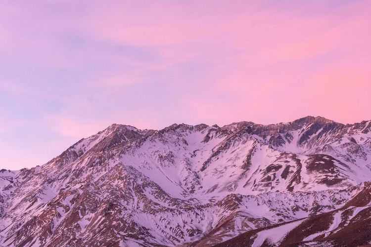 Scenic view of snowcapped mountains against pink sky during sunset