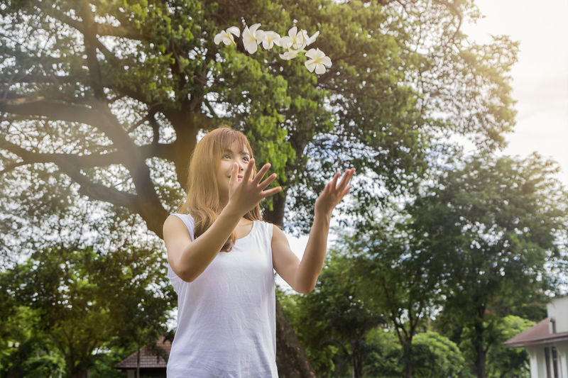 Low angle view of young woman throwing white flowers in yard