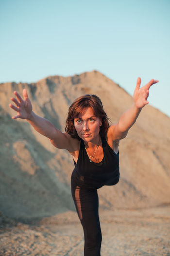young woman doing warrior 3 yoga pose Sky Land Standing Young Adult Lifestyles Leisure Activity Nature Arms Outstretched Front View Portrait Environment Women Arms Raised Outdoors Freedom Vertical Yoga Fit Care Practicing Balance Virabhadrasana 3 Desert Workout Position