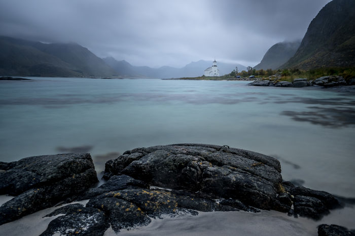 Beach Beauty In Nature Church Cold Temperature Day Gimsoy Gimsøy Kirke Lake Landscape Lofoten Lofoten Islands Mountain Mountain Range Nature No People Outdoors Rock - Object Rocks Rocks And Water Scenics Sky Tranquil Scene Tranquility Water