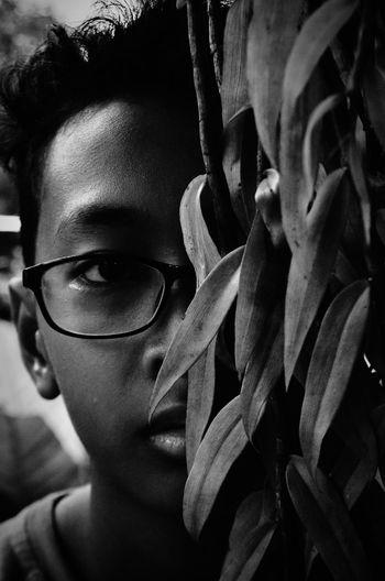 Close-up portrait of man by plant