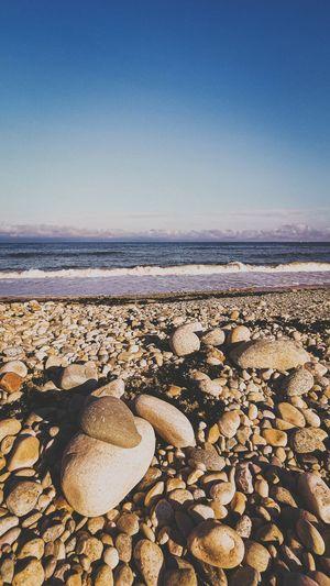 Stones on beach against clear sky