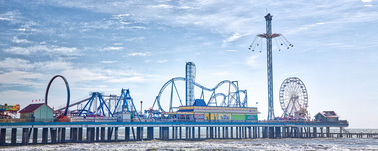 Panoramic Shot Of Amusement Park On Pier Against Sky