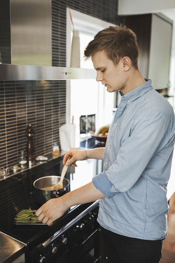 Side view of young man preparing food in kitchen
