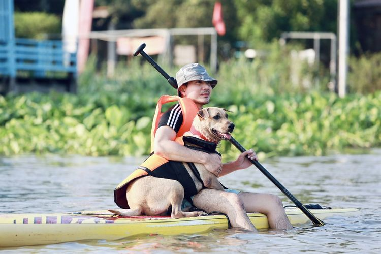 Woman with dog sitting by water