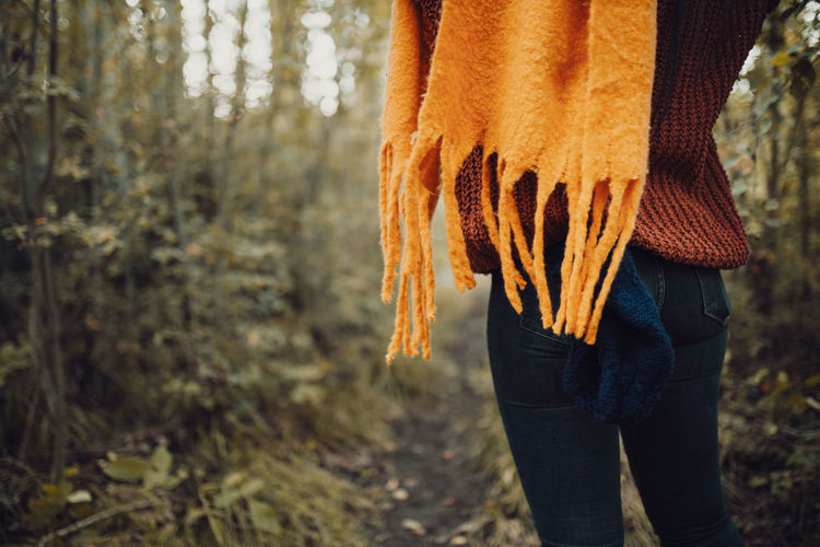 Midsection of woman standing in forest