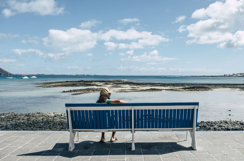 Man sitting on bench at beach against sky