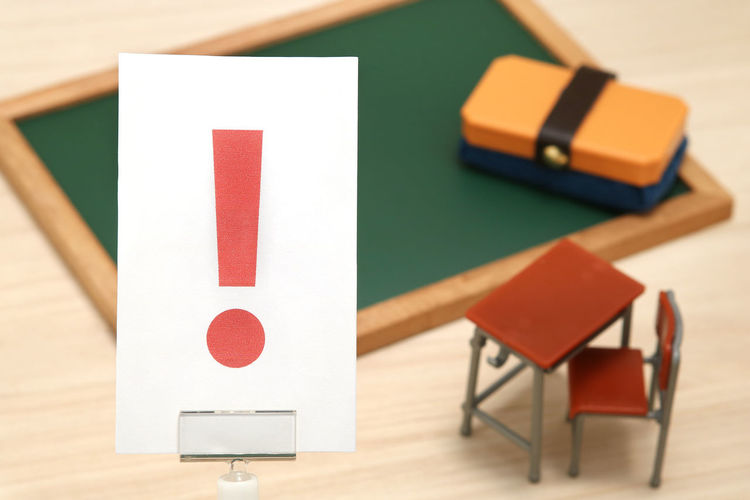 High angle view of exclamation point on paper against school supply toys in classroom