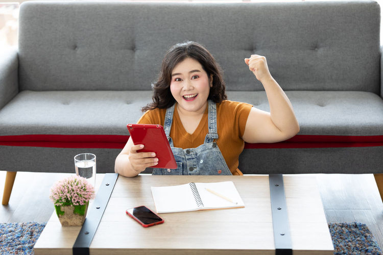 Portrait of smiling young woman sitting on sofa at table