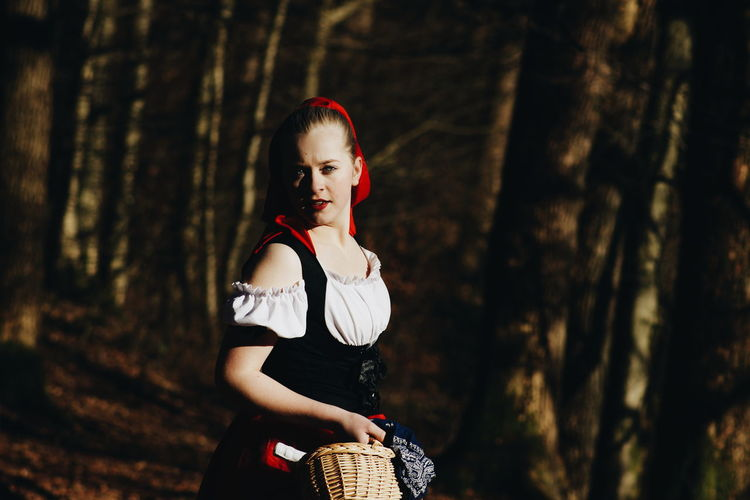 Portrait of woman in costume standing in forest