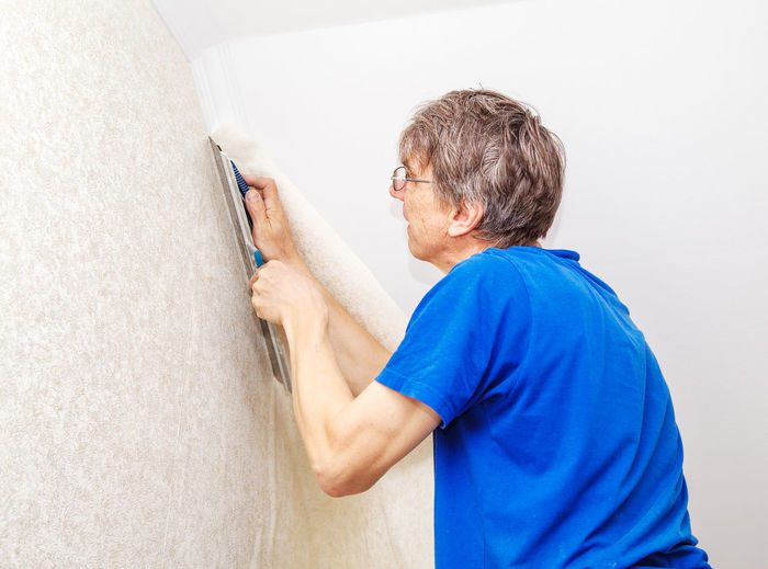 Man Putting Wallpaper On Wall At Home