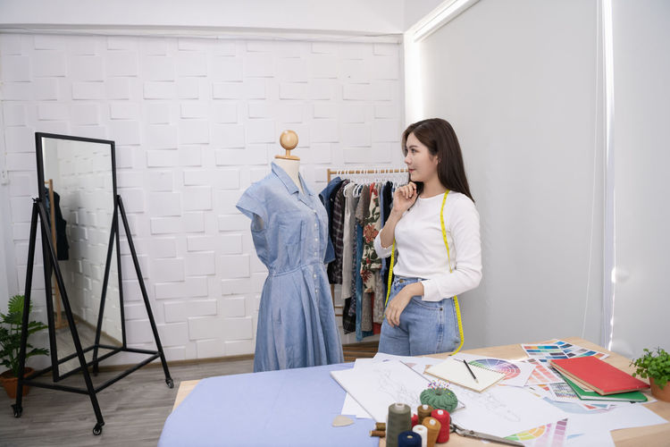 Young woman dressing mannequin while standing against wall in fashion studio