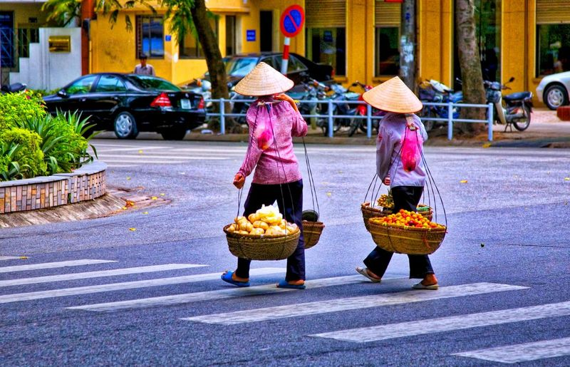 Vietnamese Women selling fruits & vegetables City Street Real People Transportation Road Women Food Architecture Adult Rear View Clothing Building Exterior For Sale Hat Food And Drink Traditional Clothing Built Structure Mode Of Transportation Retail  Day