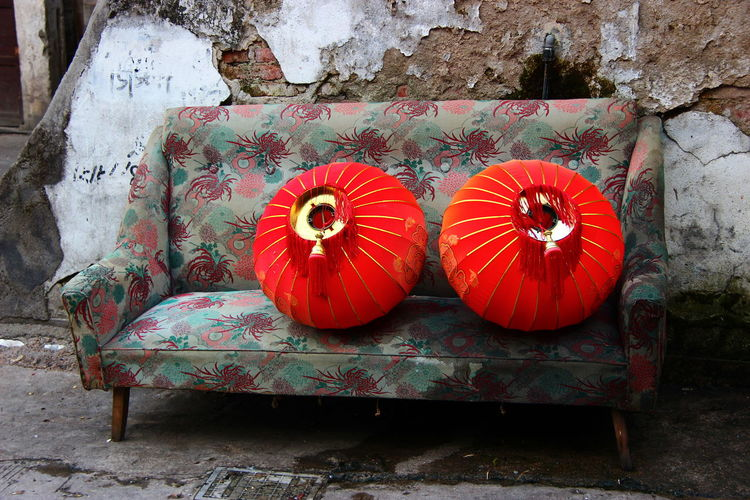 Chinese Lanterns On Sofa Against Abandoned Wall
