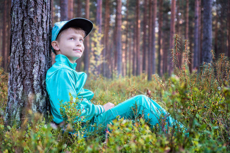 Happy boy sitting in the forest and dreaming for future Dreaming Finland Happiness Nature Casual Clothing Child Childhood Children Only Cute Evening Forest Forest Photography Grass Happiness Mood Nature One Boy Only One Person Outdoors People Portrait Sitting Smiling Tree Tree Trunk