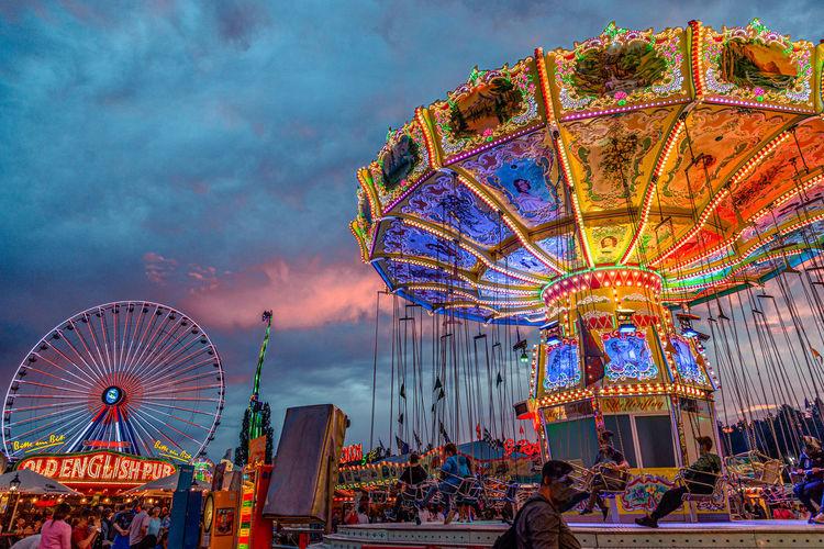 People at amusement park ride against sky