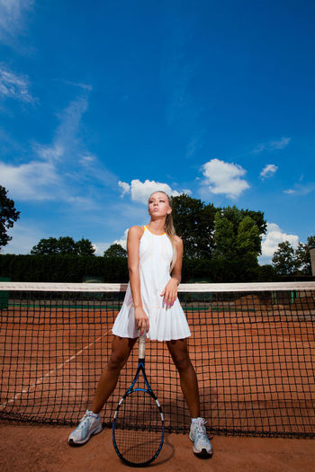 Beautiful athletic young woman in a white tennis suit leaning on the racket One Person Court Sport Sky Racket Full Length Tennis Tennis Racket Young Adult Women Cloud - Sky Lifestyles Nature Leisure Activity Young Women Standing Clothing Day