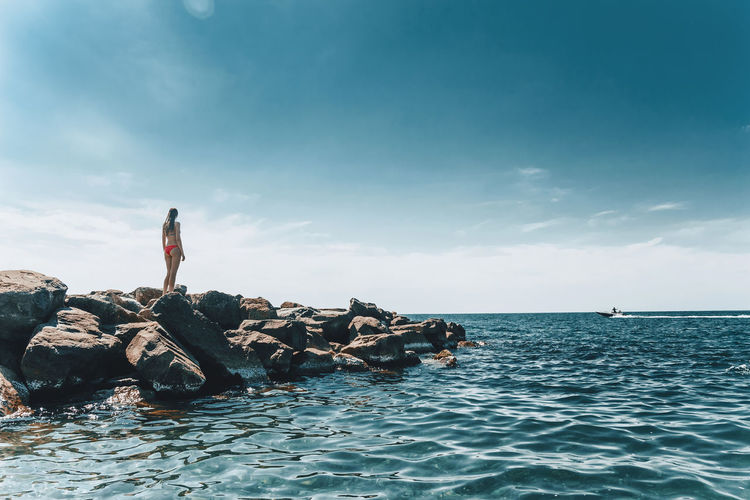 Rear View Of Bikini Woman Standing On Rocks By Sea Against Sky