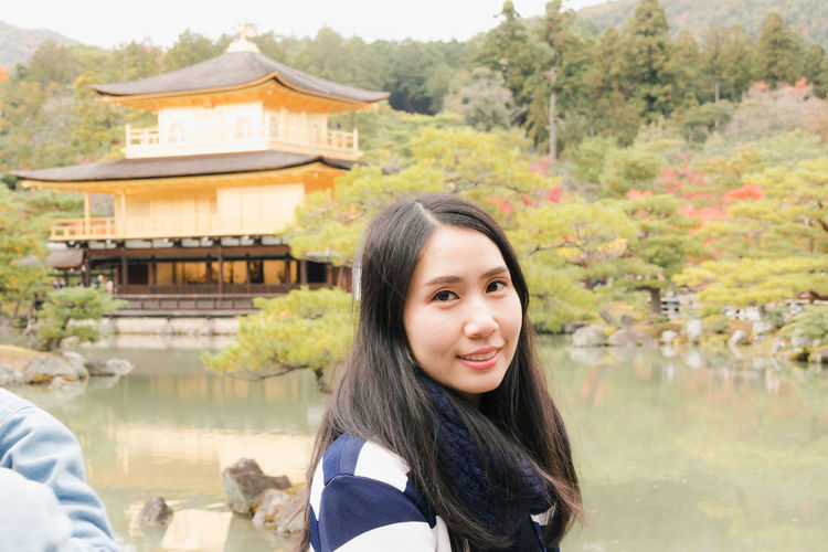Kinkakuji Temple Architecture Building Exterior Built Structure Day Lake Leisure Activity Lifestyles Looking At Camera Nature One Person Outdoors Portrait Real People Smiling Travel Destinations Tree Water Young Adult Young Women