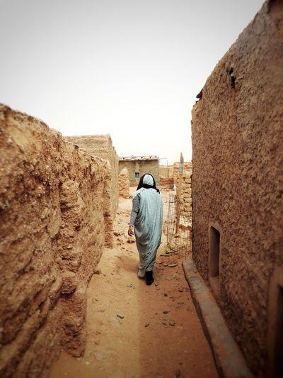 Full length rear view of man walking against wall