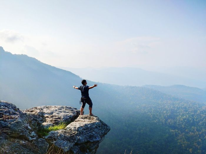 Man standing with arms outstretched at mountain against sky