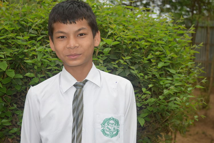Portrait of smiling young man wearing school uniform standing against plants