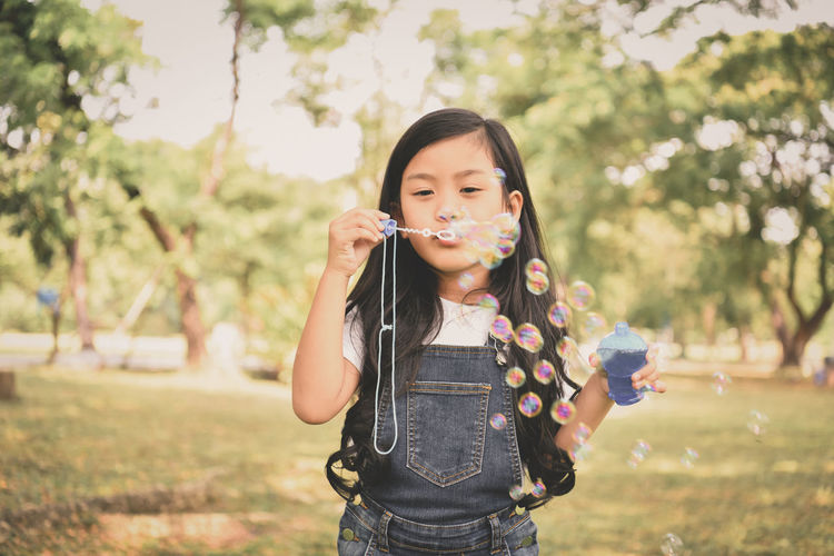 Blowing Bubble Bubble Wand Casual Clothing Child Day Field Focus On Foreground Front View Holding Innocence Leisure Activity Lifestyles Looking At Camera Nature One Person Outdoors Plant Real People Standing
