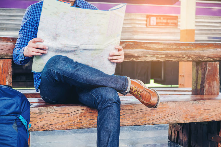 Low section of man reading map while sitting on bench at railroad station