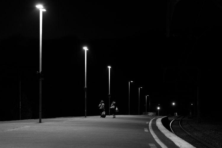 Man with illuminated street light on road at night