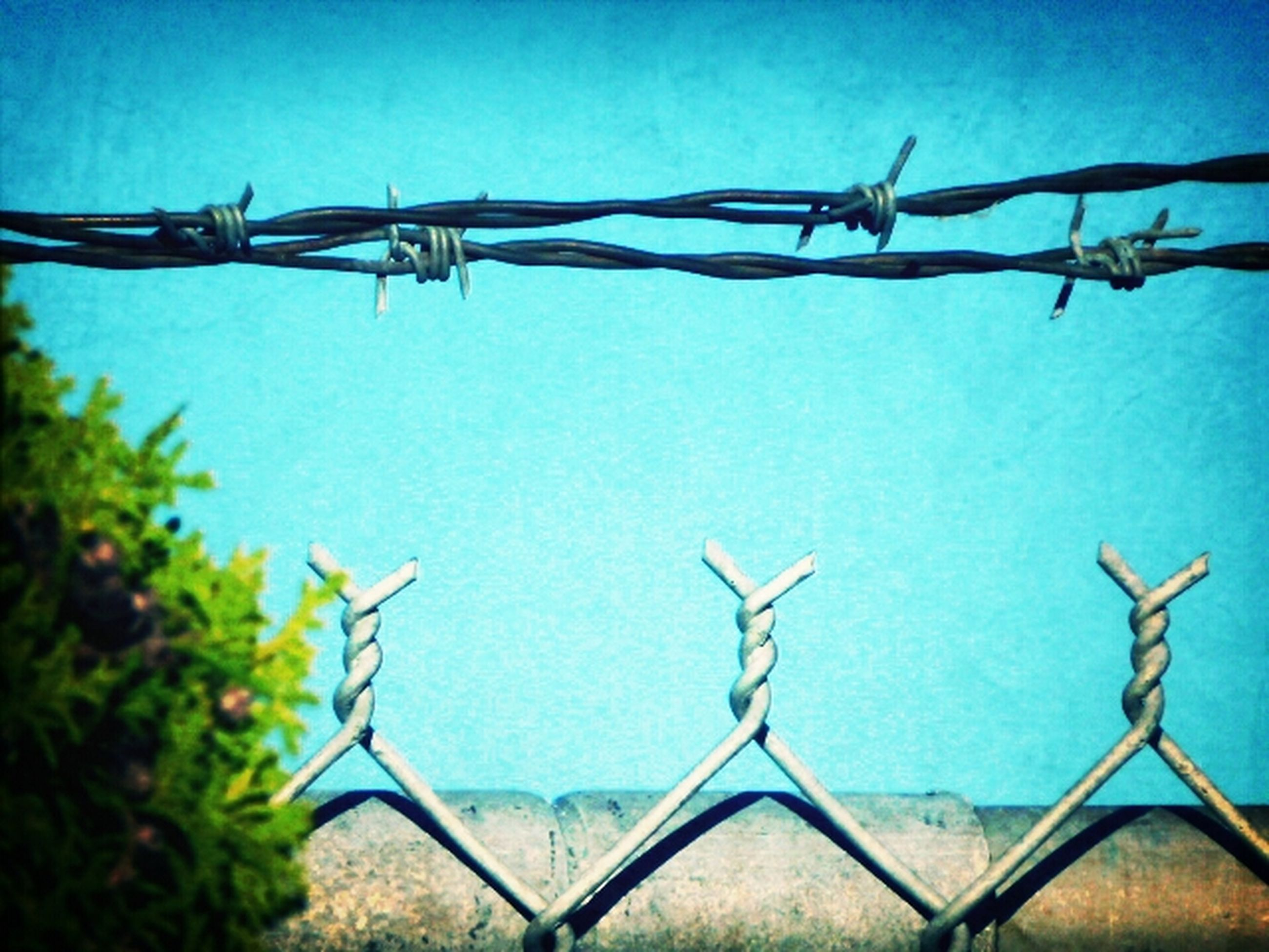 protection, clear sky, safety, fence, security, blue, barbed wire, built structure, metal, architecture, low angle view, chainlink fence, day, rope, outdoors, no people, building exterior, sky, sunlight, close-up