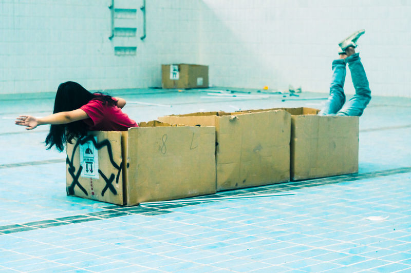 Playful friends playing with cardboard boxes on tiled floor
